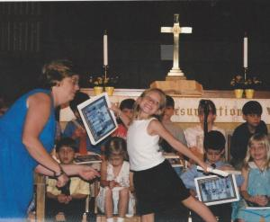 Me at my kindergarten graduation, posing with my diploma.